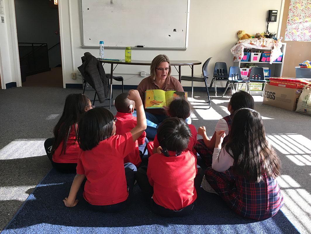 Una mujer lee un libro a un grupo de niños con discapacidad auditiva.