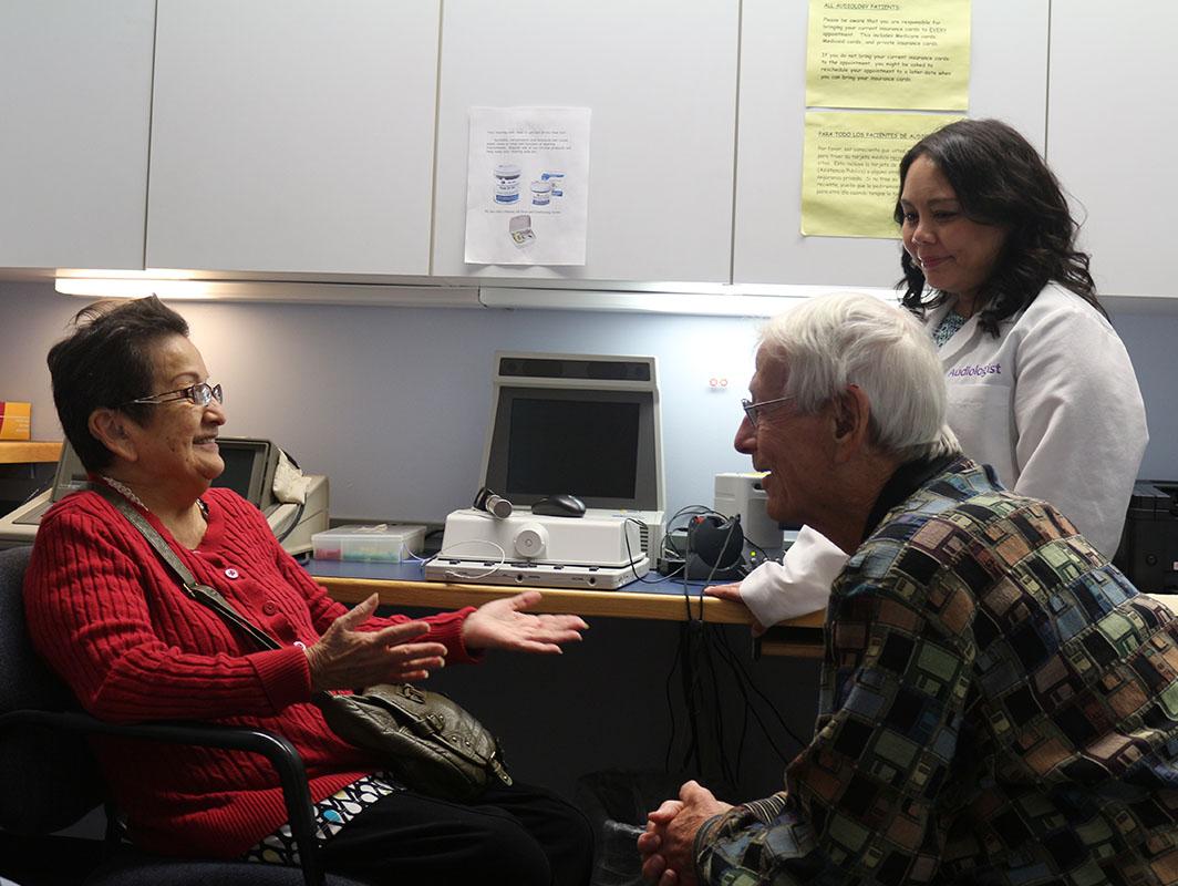 Reunión de un señor y una señora mayores con una audióloga de la Sociedad Auditiva de Chicago. ¡Ambiente cordial y amistoso!