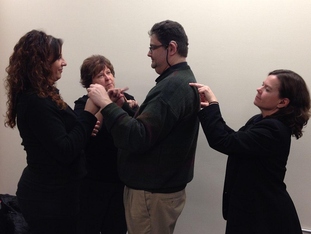 Una intérprete de la Sociedad Auditiva de Chicago trabaja con un hombre con lenguaje de señas.