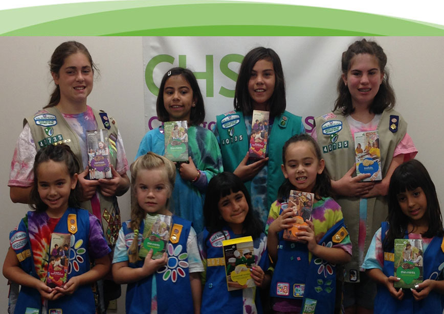 A very happy group of girls scouts holding up girls scout cookies. Chicago Hearing Society loves to help the community.