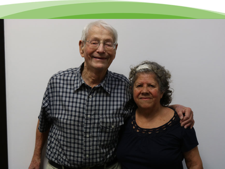 A elderly man and woman with their arms around each other smiling because they received help from Chicago Hearing Society.