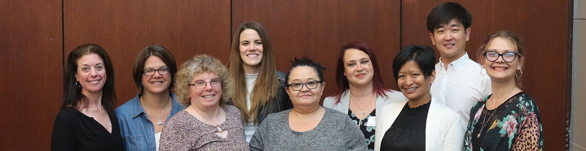 Un grupo de empleados y voluntarios de la Sociedad Auditiva de Chicago sonriéndole a usted.
