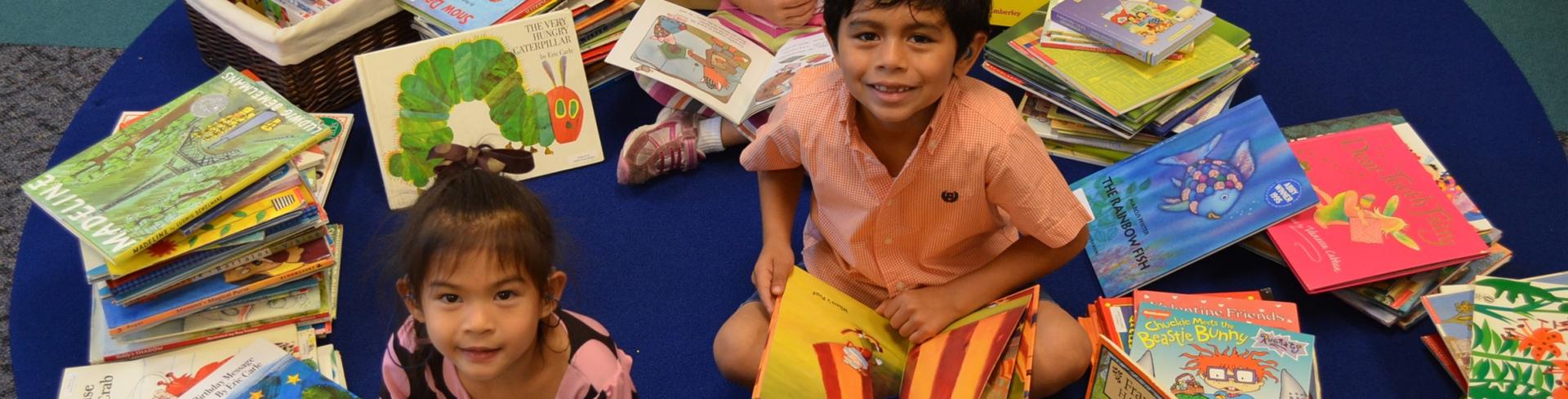 ¡Un niño y unas niñas pequeños revisan una pila de libros con grandes sonrisas!