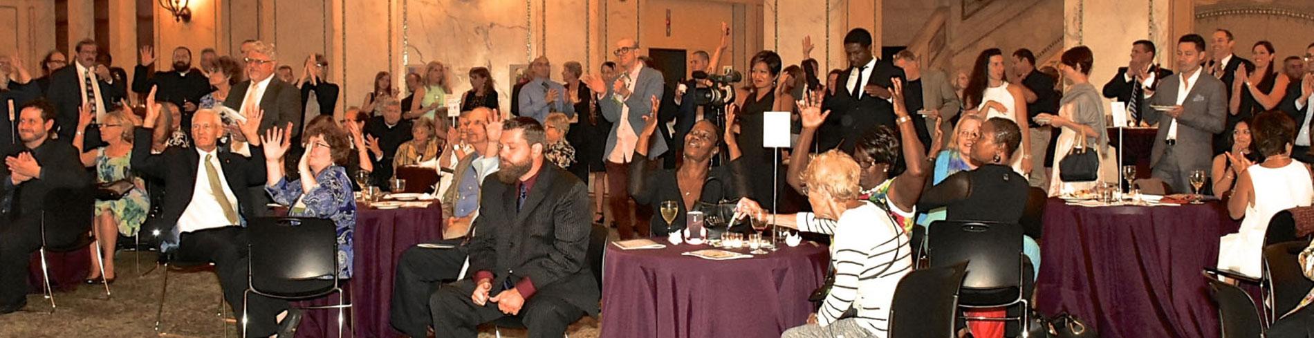 Un gran evento realizado por la Sociedad Auditiva de Chicago para ayudar a recaudar fondos. Mucha gente feliz levanta sus manos para ofertar para artículos en subasta.