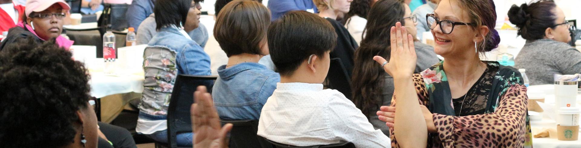 Una mujer usa lenguaje de señas para comunicarse con gente que asiste a un evento. Todos están sonriendo y divirtiéndose.
