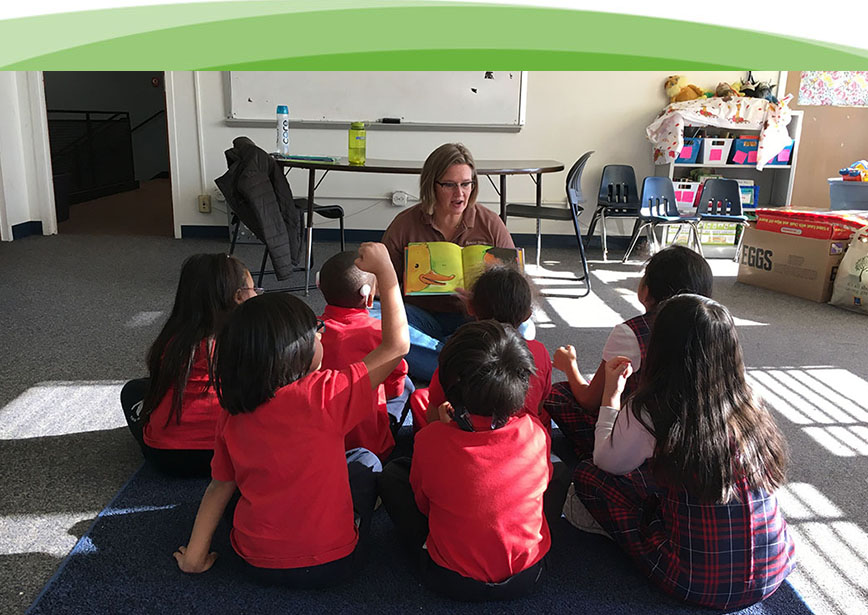 A woman is reading a book to a group of children with identified hearing loss.   Everyone is having a great time!