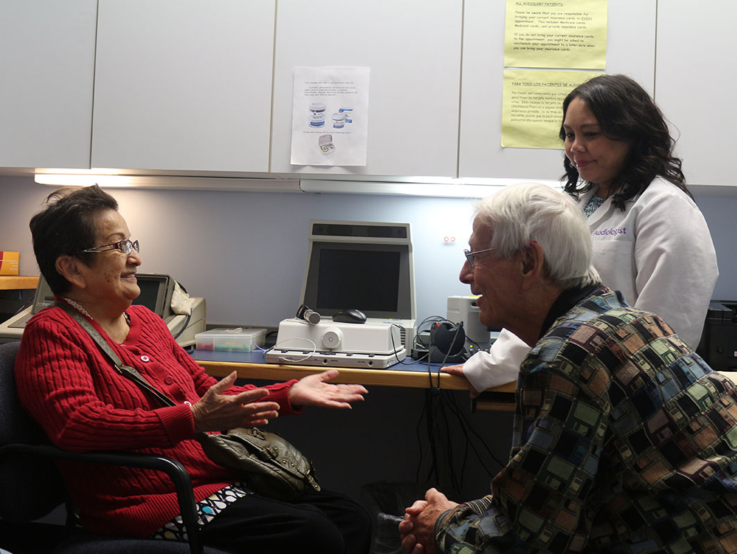 An older man and woman meeting with the Chicago Hearing Society's audiologist. All are very happy!