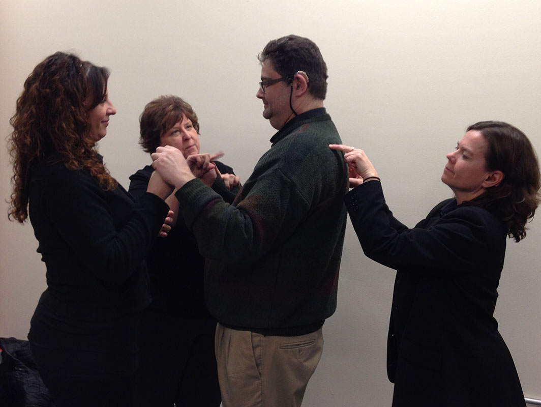 The Chicago Hearing Society's interpreter is working with a man using sign language.