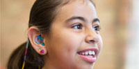 A picture of a young girl wearing hearing aids and attending a workshop.