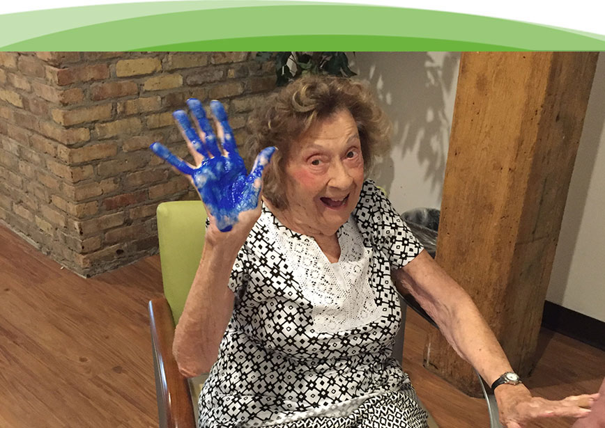 An elderly woman takes time to pose for a picture with blue paint on her hand.