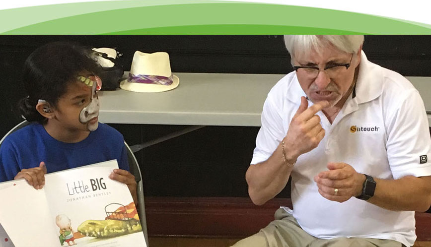 An older man is working as an interpreter for a group of children while a book is being read.