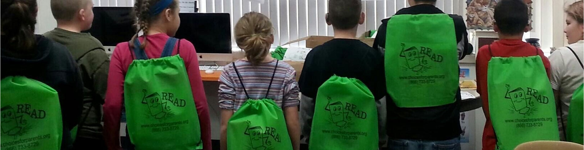 A lot of happy children all wearing green backpacks and facing computes in the Hear The Cheers Program