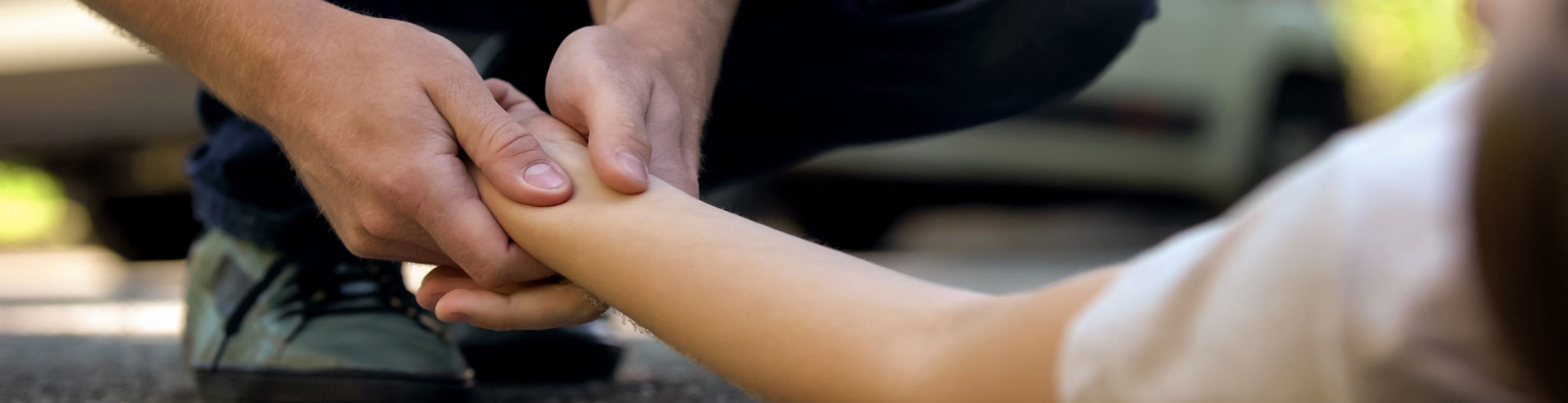 A man is checking a woman's pulse to make sure she is okay after an attack. If you're a victim we can help you.