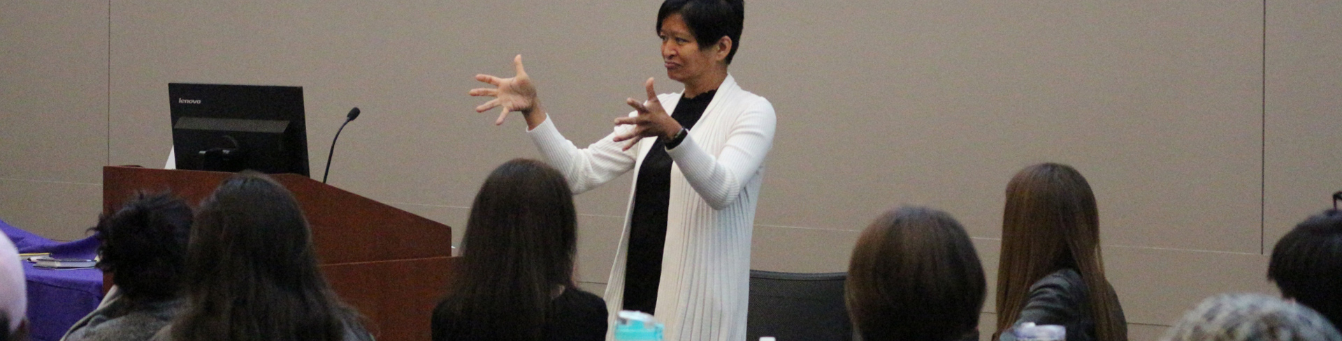 A women is providing some training on Sign Language to a group of people.