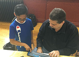 A young boy is being taught how to use a caption phone at the Chicago Hearing Society.