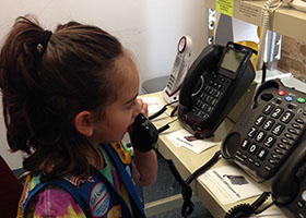 A Girl Scout is using one of the FREE amplified telephones at the Chicago Hearing Society.